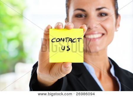 "Beautiful businesswoman showing ""contact us"" text on a post-it"