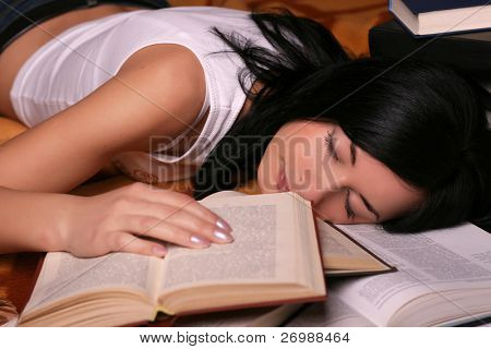 Girl lies on the floor of books