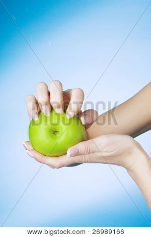 Picture of a girl who seized nails the green apple on a blue background