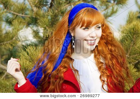 The image of a beautiful red curly girl against the backdrop of green trees in a sunny day