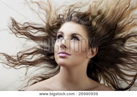 Images of beautiful glamorous girl with long hair flowing in the wind