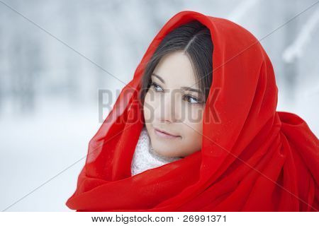 The image of a beautiful girl in winter forest in red