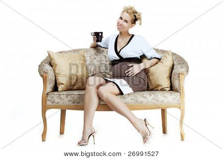 The image of a beautiful pregnant girl sitting on the sofa with a cup in his hands