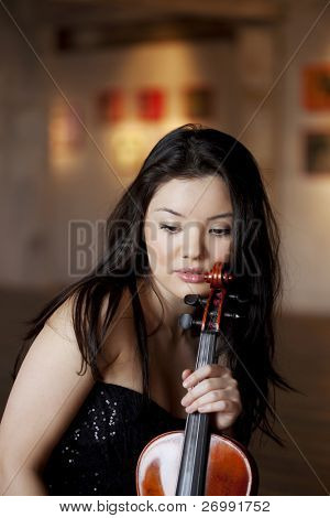 The image of a beautiful asian girl with a violin on the parquet floor