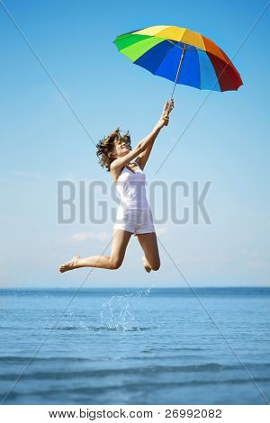 The image of a beautiful girl who jump with a rainbow umbrella