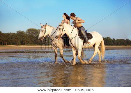 Image of a man and a woman in love with the sea on horseback