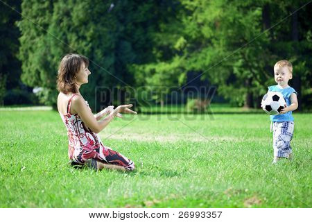 Image of family, mother and son playing ball in the park