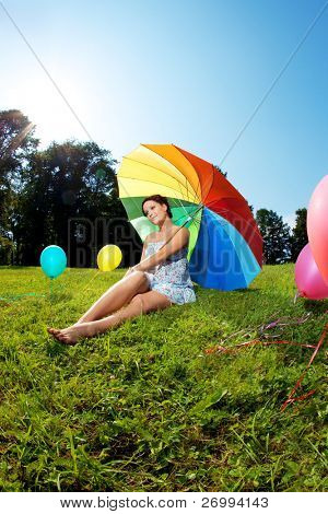 Pregnant woman with balloons in the park with a rainbow umbrella