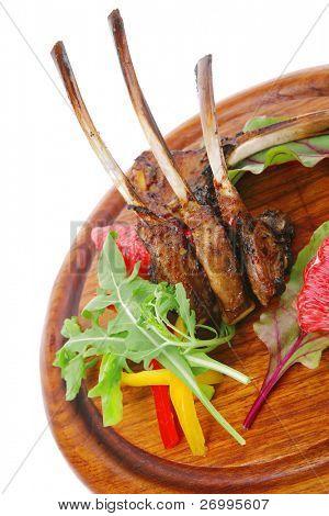 Hauptteil: gegrillte Rippen auf Holzplatte isoliert auf weißem Hintergrund mit Salat Blätter und rot