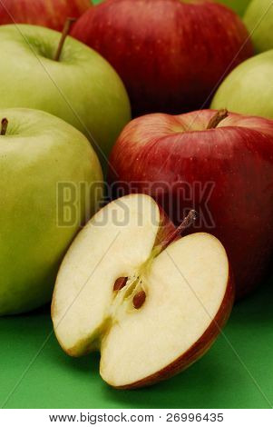 Still life with several types of apples and half apple.