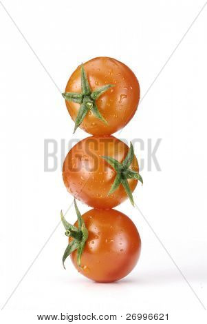 Three small tomatoes on white background.