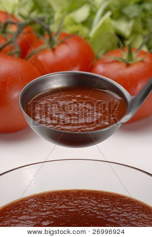 Metallic spoon with boiled fresh tomato cream on it. Pouring fresh tomato cream