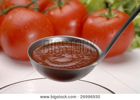 Metallic spoon with boiled fresh tomato cream on it. Pouring fresh tomato cream
