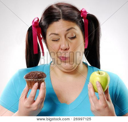 One young fat woman holding a chocolate cake and apple.