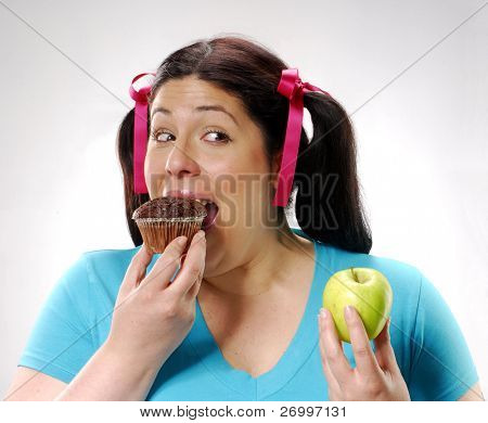 One young fat woman holding a chocolate cake and apple.Young woman eating a chocolate snack cake.
