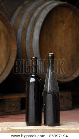 Two red wine bottles and barrels.