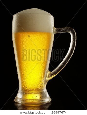 Glass of fresh beer on black background