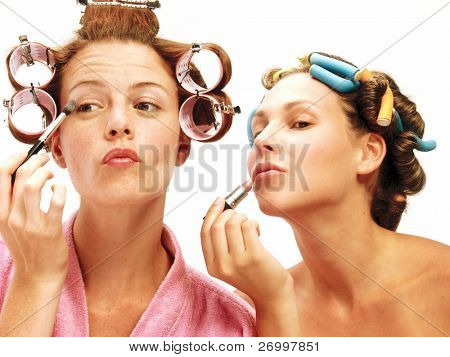 Two young women applying makeup mirror.