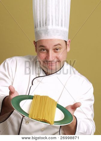 young chef holding a pasta plate.