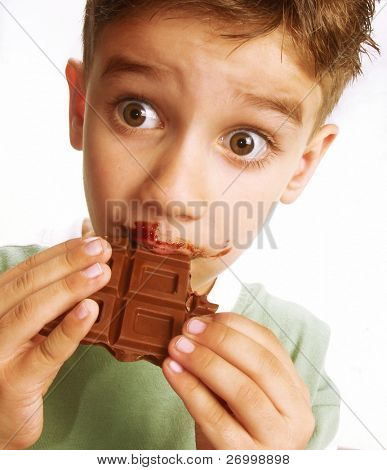 Close Up of Young Boy Eating A chocolate bar.