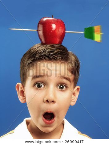 Funny little boy with a red apple and arrow on his head