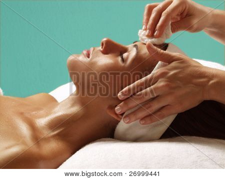 Beautiful young woman getting a face treatment at beauty salon.