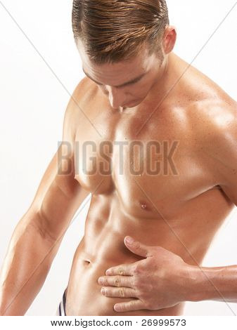 Young shaped man touching his abdomen on white background.