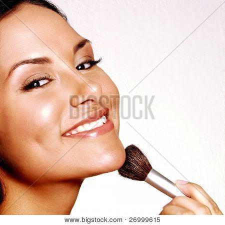 Mujer Latina aplicación de polvos de maquillaje sobre fondo blanco, maquillaje de la mujer Latina.
