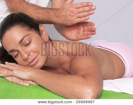 Closeup of a beautiful young Hispanic woman receiving shoulder massage at spa