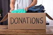 Young Man Donating Clothes In Donation Box Over Wooden Desk poster