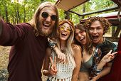 Image of cheerful hippie people men and women taking selfie in forest near retro minivan poster