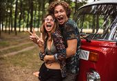 Joyful hippie couple man and woman smiling and hugging each other while standing near minivan in for poster