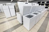 Rows of white top loading freezers and fridges in appliance stores showroom poster