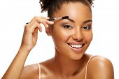 Smiling Girl Using Brush For Eyebrows. Photo Of Young African American Girl On White Background. You poster
