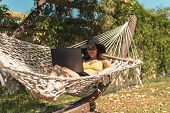 Young Woman In Yellow Swimsuit And Hat Lying In Hammock With Laptop, Work On Vacation, Freelance, Re poster