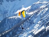 image of ultralight  - A flying paraglider in mountains in the winter - JPG