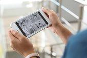 Woman Monitoring Modern Cctv Cameras On Smartphone Indoors, Closeup poster