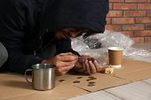 Poor Man Counting Coins On Floor Near Brick Wall poster