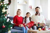 Happy young casual family with giftboxes looking at you while enjoying xmas eve at home poster