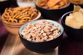 Salty snack including peanuts, potato chips and pretzels served as party food in bowls poster