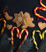 New Year And Christmas Background. Christmas Gingerbread, Candy Cane Hearts, Blue Fir Tree Branches  poster