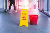 Yellow Caution wet floor sign on wet floor with red bucket poster