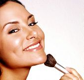 Latin woman applying makeup powder on white background,latin woman makeup.