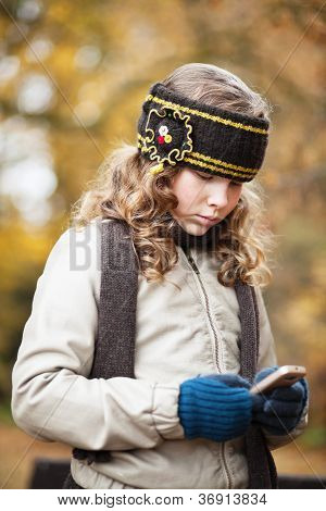 Girl Texting With Cellphone In An Autumn Park