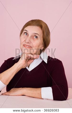 Pretty elderly  Caucasian business woman sits dreaming