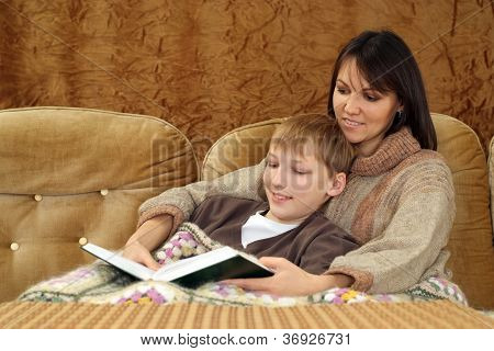 A happy Caucasian mother with her son sitting on the couch