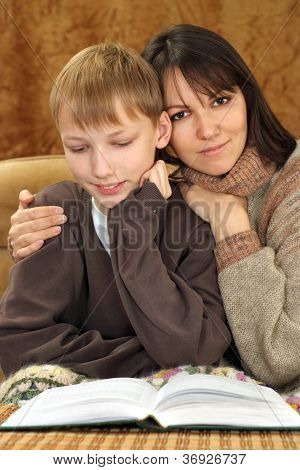 Beautiful luck Caucasian mother with her son reading a book