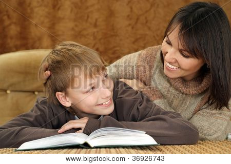 Beautiful joy Caucasian mother with her son reading a book