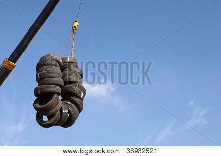 Used tyres hanging on a crane