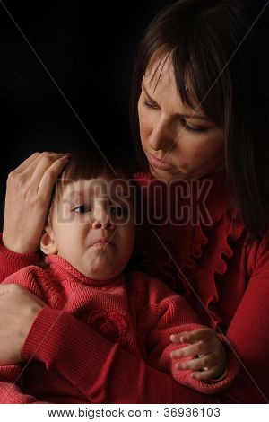 A beautiful Caucasian mother with a sad crying daughter